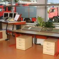 biurka, kontenery biurowe i pojazdy wielkogabarytowe za oknem