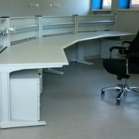 stanowisko operatorskie na które składa się krzesło biurowe czarne na kółkach oraz biurko łamane z instalacją pozwalającą zawiesić monitory